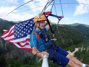A young lad riding down the zipline with a US Flag. God bless America!