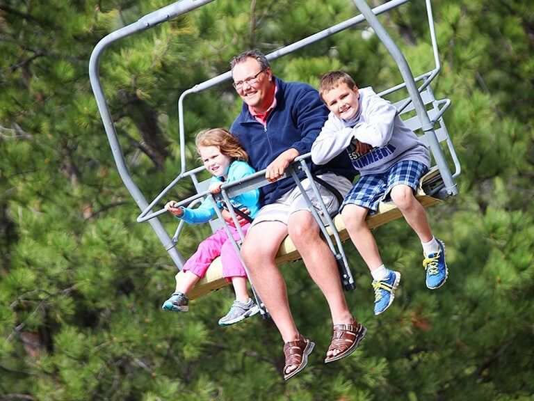 Dad with two kids on the chairlift. It's a sunny day in the Black Hills and they are all enjoying their little vacation!