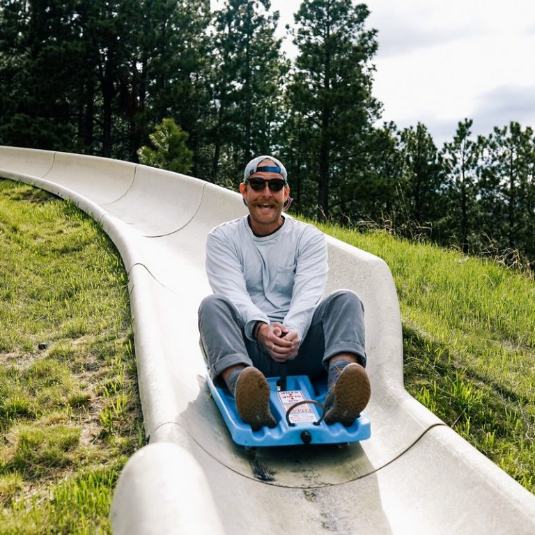 man going down the tubing hill with a huge smile on his face. he's having a blast!
